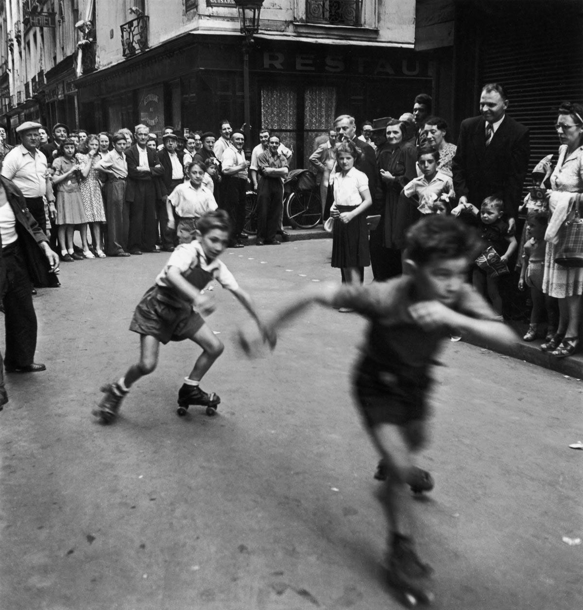 Doisneau - Course de patins a? roulettes, Paris, 14 juillet 1949