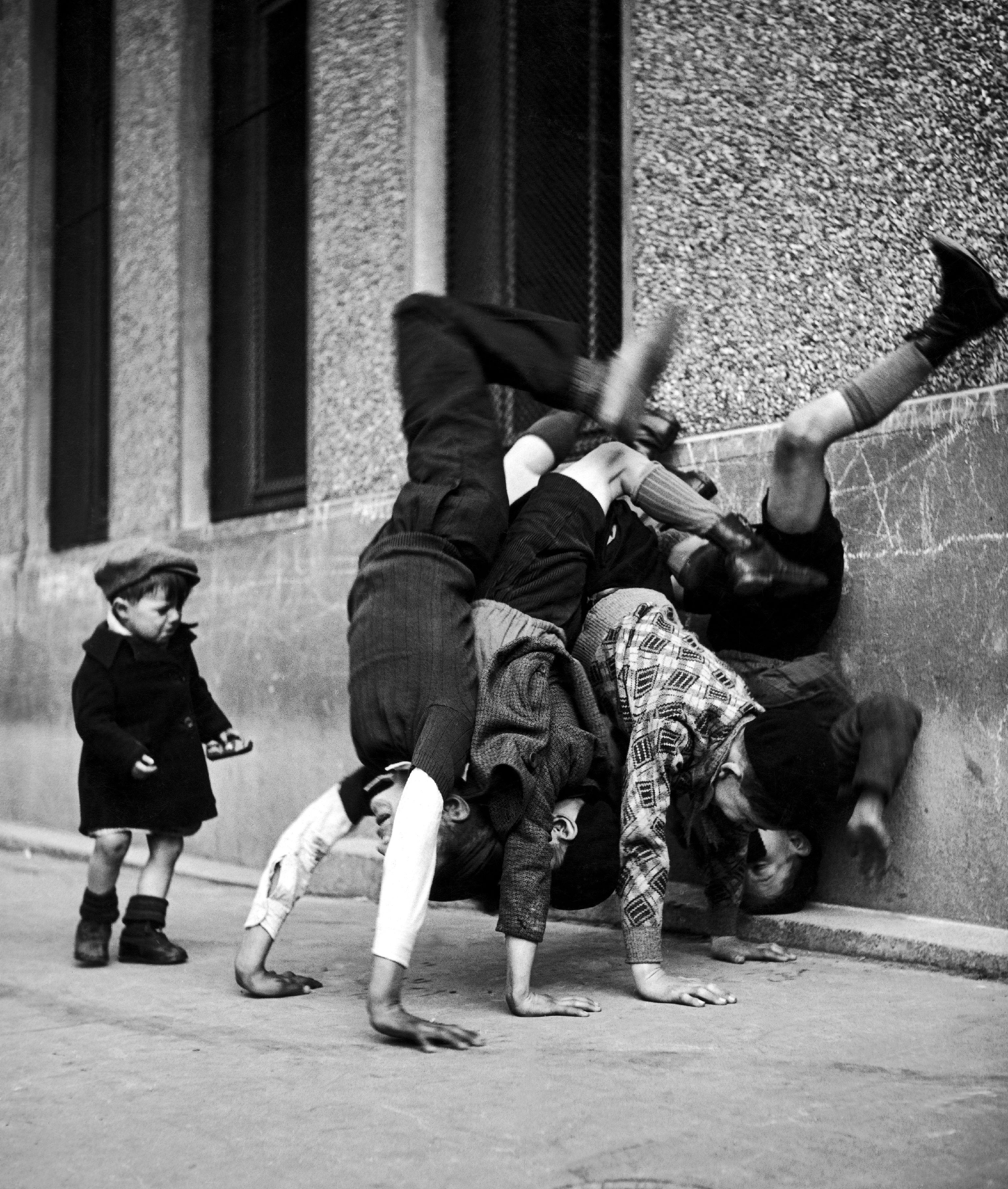 Enfants jouant à faire le poirier, rue des peupliers, 1934, Paris 13ème, France.